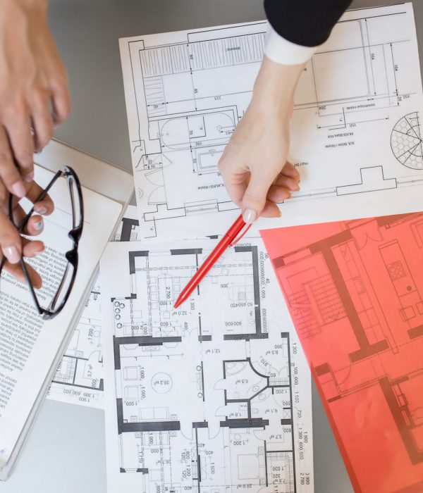 Above view close up of unrecognizable people pointing at house plans on table in real estate agency